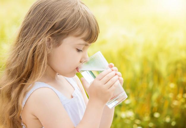 bambina che beve acqua trattata in un campo di grano 2