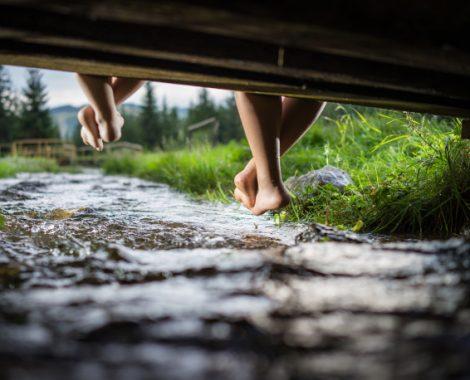 bambini su un ponte con sotto un ruscello d'acqua