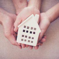 mani-del-bambino-e-dell-39-adulto-che-tengono-concetto-bianco-del-riparo-della-casa-della-casa-di-famiglia-e-del-senzatetto_49149-474